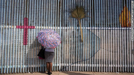 TOPSHOT - A woman talks to a relative through the border fence during the holiday weekend near the US-Mexico border in Playas de Tijuana, on April 16, 2017, in Tijuana, northwestern Mexico. / AFP PHOTO / GUILLERMO ARIAS        (Photo credit should read GUILLERMO ARIAS/AFP/Getty Images)
