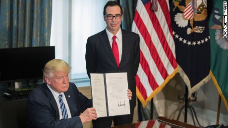 WASHINGTON, DC - APRIL 21: (AFP OUT) U.S. President Donald Trump (L), with Secretary of Treasury Steven Mnuchin (R), displays a signed financial services Executive Order during a ceremony in the US Treasury Department building on April 21, 2017 in Washington, DC. President Trump is making his first visit to the Treasury Department for a memorandum signing ceremony with Secretary Mnuchin. (Photo by Shawn Thew - Pool/Getty Images)