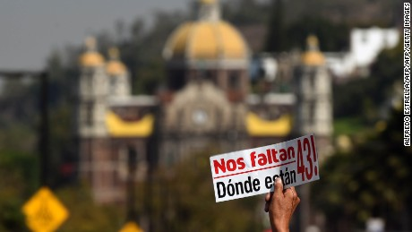 "A person marching with relatives and friends of 43 students of the Raul Isidro Burgos rural school who disappeared on September 26, 2014 in the city of Iguala, holds a sticker reading ""43 Are Missing. Where Are They?"", during a demonstration in demand of justice in Mexico City on December 26, 2016. The students, from a rural teachers college in the southern state of Guerrero, disappeared after they were attacked by local police in Iguala on September 26, 2014. / AFP / Alfredo ESTRELLA        (Photo credit should read ALFREDO ESTRELLA/AFP/Getty Images)"