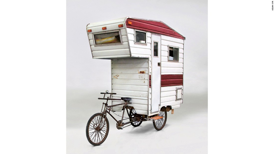 Perched on a tricycle and constructed from corrugated aluminum, plexiglas, plywood and timber, this pedal-powered concept mobile home is large enough for one person.