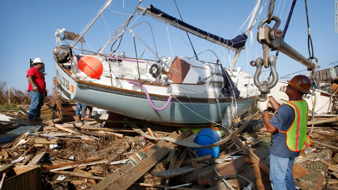 Workers prepare to remove a sailboat on September 21, 2008. Hurricane Ike pushed the vessel onto the edge of a highway in Galveston, Texas.