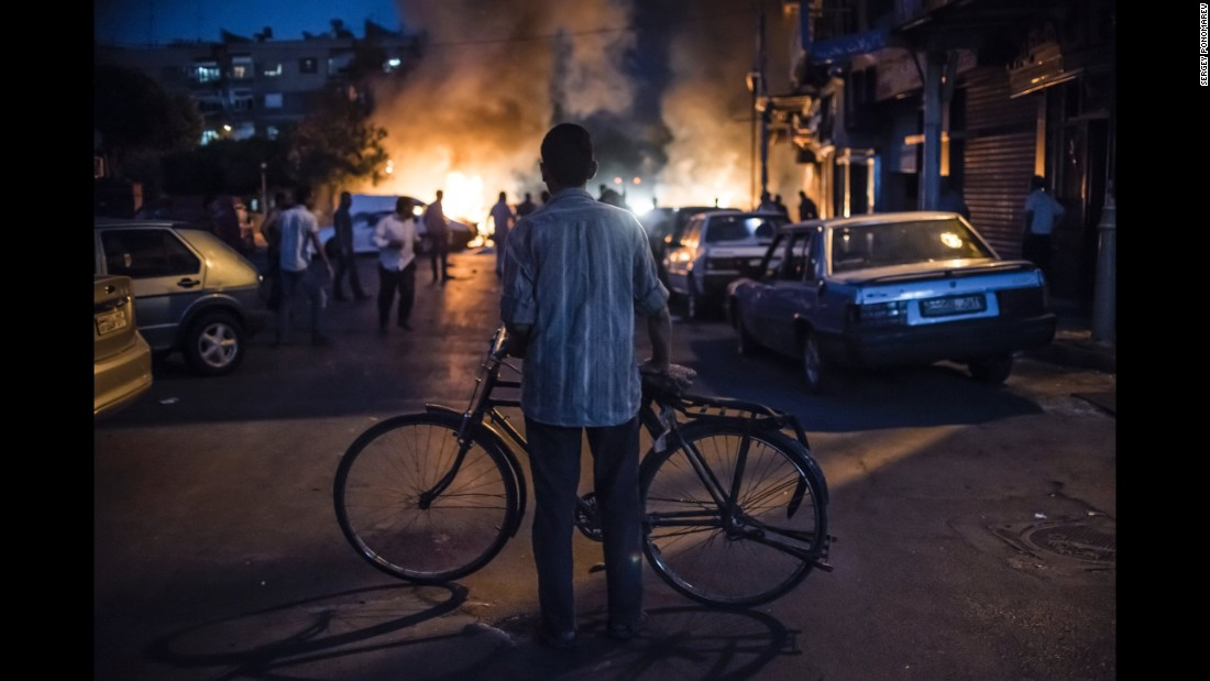 A cyclist watches a fire caused by the explosion of a mortar shell during fighting between government and opposition forces near the Old City of Damascus. (August 24, 2013)