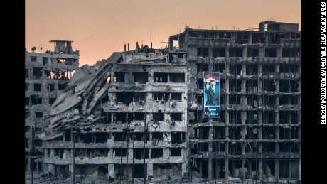 An election campaign poster for President Bashar al-Assad hangs on a ruined shopping mall in Homs.