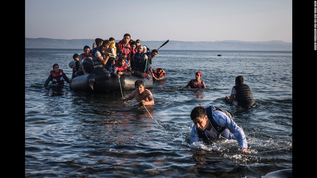 An inflatable dinghy, crowded with refugees and migrants, is pulled ashore on the Greek island of Lesbos after sailing five miles across the Aegean Sea from Turkey. (July 27, 2015)