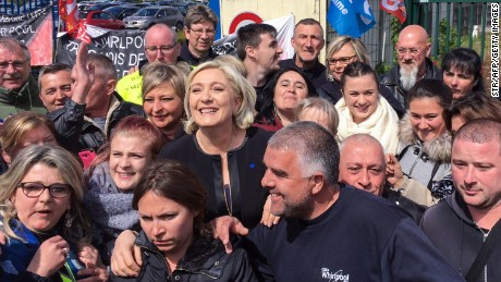 Le Pen  smiles with people in front of the Whirlpool factory in Amiens, northern France.