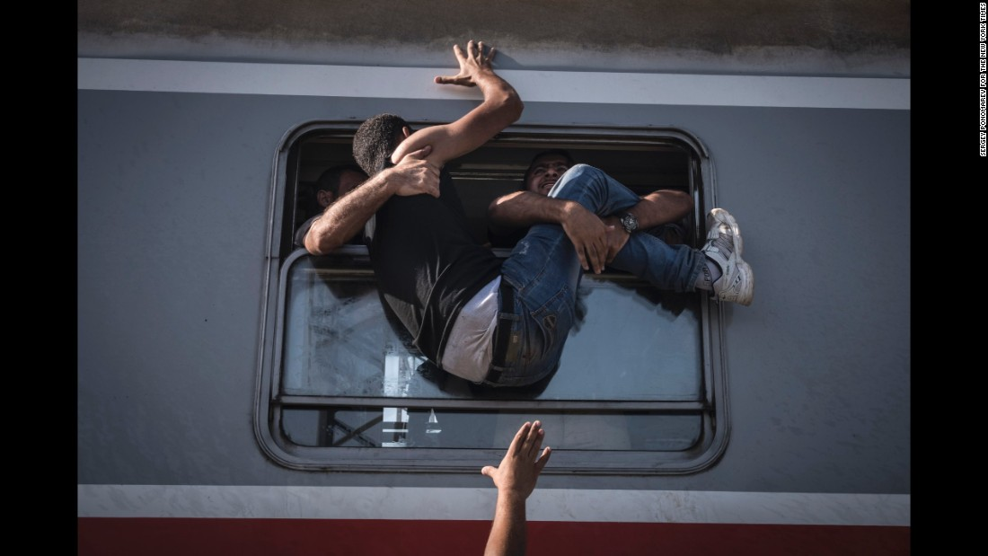 A desperate man is hauled through the window of one of the last trains to carry refugees and migrants from the Croatian border to Zagreb. (September 18, 2015)