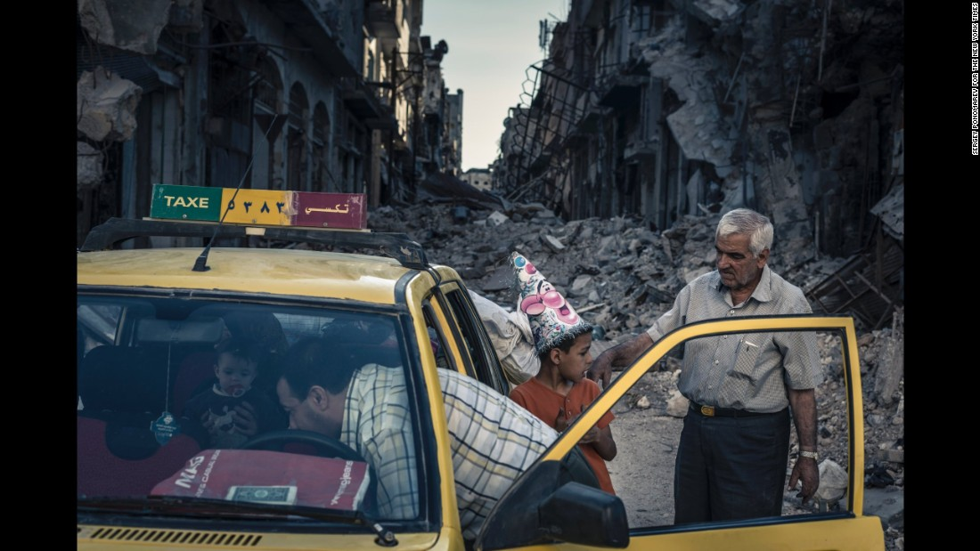 Abu Hisham Abdel Karim and his family use a local taxi to salvage possessions from their ruined apartment in the Khalidiya district of Homs shortly after the city was retaken by government forces. (June 15, 2014)