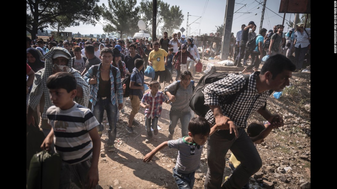 Refugees and migrants rush to board a Macedonian train to take them from the Greek border village of Idomeni towards Serbia. (July 27, 2015)