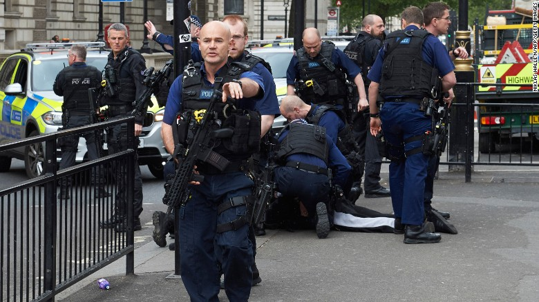 Firearms officers pin the suspect on the ground outside the Westminister undergound train station.