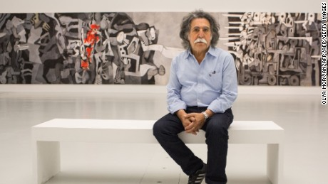 "Dia Azzawi pictured in with his work ""Mission of Destruction"" at the Arab Museum of Modern Art in Doha, Qatar (2016)."