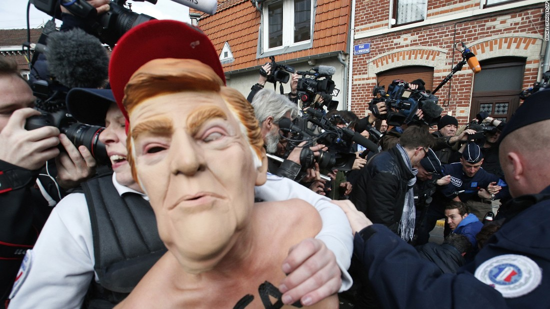 "An activist wearing a Donald Trump mask is detained as she demonstrates in Henin-Beaumont, France, where French presidential candidate Marine Le Pen would later vote on Sunday, April 23. Le Pen, leader of the far-right National Front party, <a href=""http://www.cnn.com/2017/04/24/politics/trump-french-elections-le-pen/"" target=""_blank"">has risen on the same populist politics</a> that ignited Trump's presidential campaign last year."