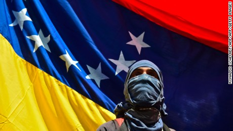 "A man attends a march paying homage to student Juan Pablo Pernalete -killed on the eve by impact of a gas grenade during a protest against President Nicolas Maduro- in Caracas, on April 27, 2017. Venezuela defied international pressure over its deadly political crisis as European lawmakers accused its government of ""brutal repression"" and US President Donald Trump called the country ""a mess"". Nearly a month of clashes at anti-government protests have left 28 people dead, according to prosecutors. / AFP PHOTO / RONALDO SCHEMIDT        (Photo credit should read RONALDO SCHEMIDT/AFP/Getty Images)"