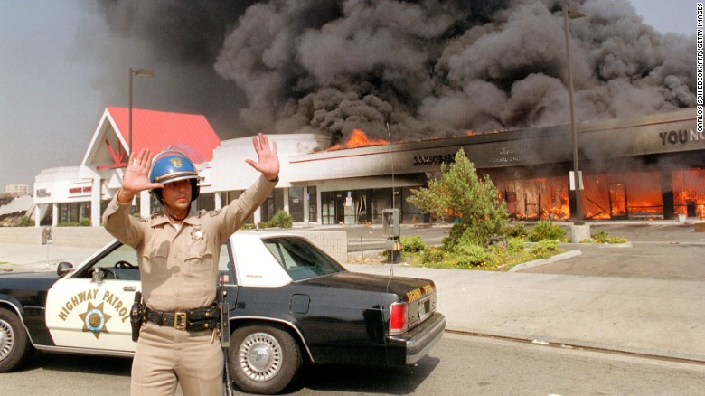 A California Highway patrolman directs raffic around a shopping center engulfed in flames in Los Angeles, 30 April 1992.