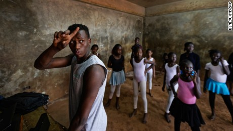 In this photo taken Friday, Dec. 9, 2016, young ballerinas practice under the instruction of Kenyan ballet dancer Joel Kioko, 16, left, in a room at a school in the Kibera slum of Nairobi, Kenya. In a country not usually associated with classical ballet, Kenya's most promising young ballet dancer Joel Kioko has come home for Christmas from his training in the United States, to dance a solo in The Nutcracker and teach holiday classes to aspiring dancers in Kibera, the Kenyan capital's largest slum. (AP Photo/Ben Curtis)