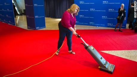 A hotel worker vacumes the red carpet prior to guests arrival at the White House Correspondents Dinner in Washington, Saturday, April 29, 2017. (AP Photo/Cliff Owen)