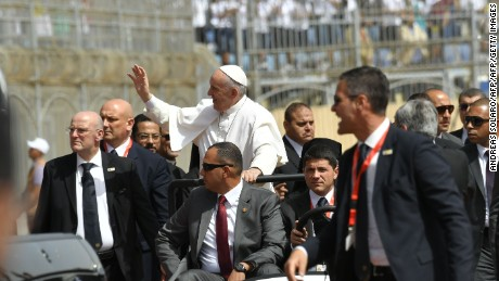 Pope Francis is surrounded by security as he rides an uncovered Popemobile before the start of a mass on April 29, 2017 at a stadium in Cairo.  Pope Francis is set to lead a mass for Egypt's small Catholic community as he visits the country in support of its Christians following a series of deadly church bombings. The spiritual leader of the world's almost 1.3 billion Catholics will lead mass for some 30,000 believers in a stadium on the outskirts of Cairo.  / AFP PHOTO / Andreas SOLARO        (Photo credit should read ANDREAS SOLARO/AFP/Getty Images)