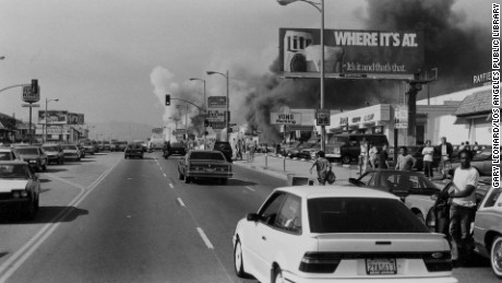 "Buildings going up in smoke on an unidentified street during the riots of 1992, following the decision in the Rodney King case. Film still from ""LA 92."""