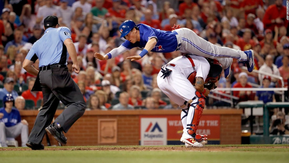 Toronto's Chris Coghlan leaps over St. Louis catcher Yadier Molina to score a run on Tuesday, April 25.