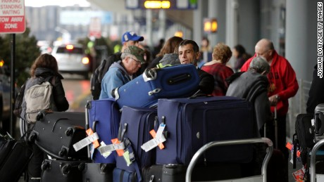 CHICAGO, IL - DECEMBER 23 : An airport worker organizes luggage on a cart as travelers in the back ground and in the pre check-in line at O'Hare International Airport on December 23, 2016 in Chicago, Illinois. O'hare International Airport is one of the busiest hubs in the nation during the weeks surrounding Christmas and New Years.  (Photo by Joshua Lott/Getty Images)
