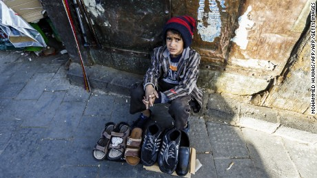 A Yemeni child peddlar sells shoes in Sanaa's Suq Al-Melh (Salt Market) on January 24, 2017. Scores of Yemeni children orphaned by the war are now deployed at road junctions begging for the little that would feed them and their siblings.   / AFP / TO GO WITH AFP STORY BY JAMIL NASSER        (Photo credit should read /AFP/Getty Images)