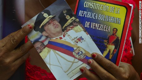 "A supporter shows a Venezuelan Constitution and a picture of late President Hugo Chavez as President in Charge Nicolas Maduro (not depicted) speaks during the official registration of his candidacy for the upcoming presidential election at the National Electoral Council (SNE) in Caracas, on March 11, 2013. Venezuela has entered a bitter election race to succeed Hugo Chavez, with his chosen successor branding his challenger a ""fascist"" after the opposition candidate accused him of exploiting the late leader's death. AFP PHOTO/Luis Acosta        (Photo credit should read LUIS ACOSTA/AFP/Getty Images)"