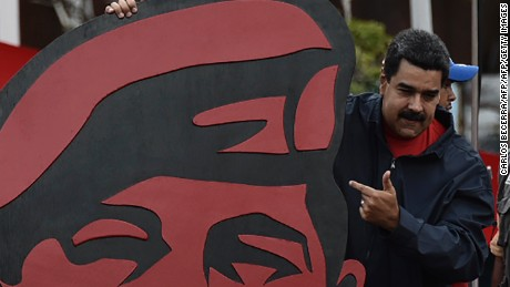 Venezuelan President Nicolás Maduro points to a placard of his mentor, the late Hugo Chavez, in a May Day rally in Caracas.