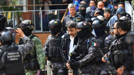 "Agents of the Criminal Investigation Agency and soldiers of the Mexican army escort senior lieutenant of US jailed drug lord, Joaquin ""Chapo"" Guzman, Damaso Lopez (C) after arresting him, in Mexico City on May 2, 2017.   Mexico announced the arrest of a senior lieutenant of the jailed Joaquin ""Chapo"" Guzman who was allegedly engaged in a bloody struggle to lead the Sinaloa crime syndicate.  / AFP PHOTO / STR        (Photo credit should read STR/AFP/Getty Images)"