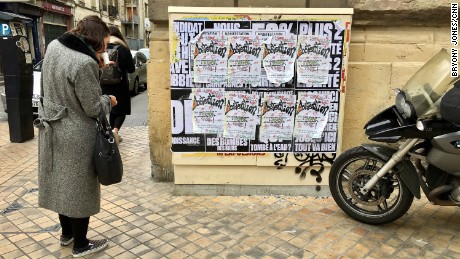 A woman in Bordeaux reads posters urging voters not to turn out this weekend.