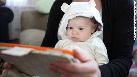 A two month old baby girl watches an interactive app for babies on an iPad while held by her mother. Photo Tim Clayton (Photo by Tim Clayton/Corbis via Getty Images)