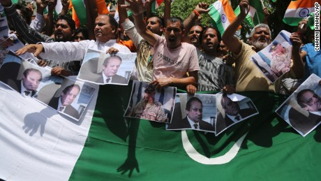Hindu nationalists hold pictures of Pakistan Prime Minister Nawaz Shariz while shouting anti-Pakistan slogans during a rally in Jammu, India Tuesday.