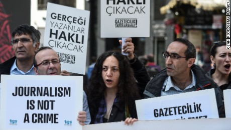 "Journalists hold placards reading ""journalists will be freed , they will write again"" during a demonstration for the World Press Freedom Day on the Istiklal avenue, in Istanbul, on May 3, 2017."