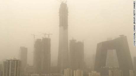 Central Beijing sits under a thick layer of smog Thursday, as a sandstorm swept north east China.