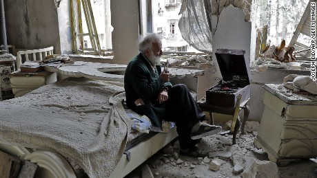 TOPSHOT - Mohammed Mohiedin Anis, or Abu Omar, 70, smokes his pipe as he sits in his destroyed bedroom listening to music on his vinyl player, gramophone, in Aleppo's formerly rebel-held al-Shaar neighbourhood.  / AFP PHOTO / JOSEPH EID        (Photo credit should read JOSEPH EID/AFP/Getty Images)