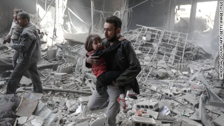 TOPSHOT - Syrian men evacuate children from the rubble of destroyed buildings following reported government airstrike on the rebel-held town of Douma, on the eastern outskirts of the capital Damascus, on February 25, 2017. Syrian regime forces carried out raids on several areas in the country, targeting mainly the besieged town of Douma, causing the deaths of at least 13 civilians, according to Syrian Observatory for Human Rights. The raids continued despite the United Nations confirmation a few days earlier that Moscow formally asked its ally Damascus to stop launching strikes during the Geneva negotiations, which began earlier in the week. / AFP PHOTO / Sameer Al-Doumy        (Photo credit should read SAMEER AL-DOUMY/AFP/Getty Images)