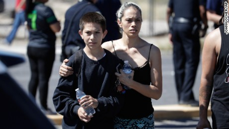 Christina Marquez picks up her son Angelo at the crash scene Thursday.