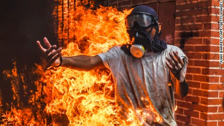 TOPSHOT - A demonstrator catches fire, after the gas tank of a police motorbike exploded, during clashes in a protest against Venezuelan President Nicolas Maduro, in Caracas on May 3, 2017.