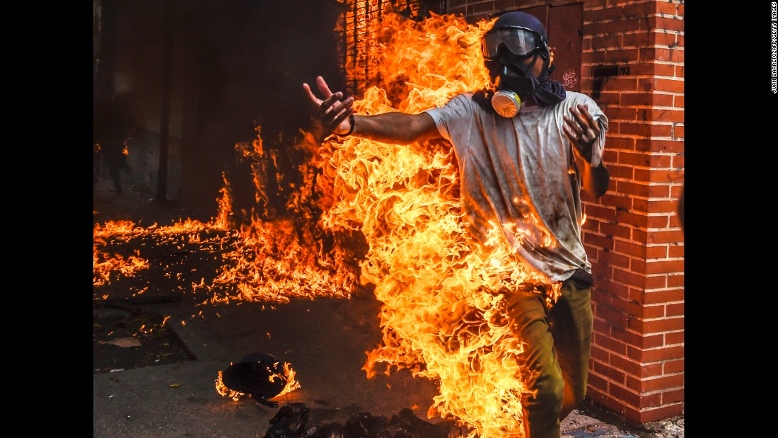 A demonstrator catches on fire during protests in Caracas on May 3. It happened as protesters clashed with police and the gas tank of a police motorbike exploded. Other photos from the scene showed the man being attended to with burns on his body.