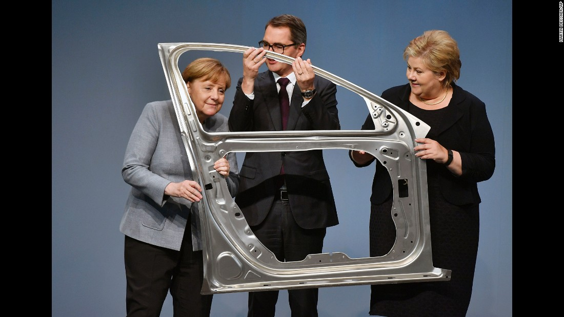 From left, German Chancellor Angela Merkel, Hydro CEO Svein Richard Brandtzaeg and Norwegian Prime Minister Erna Solberg hold an aluminum car door in Grevenbroich, Germany, on Thursday, May 4. Hydro, a Norwegian aluminum producer, was opening a new automotive line in Grevenbroich.