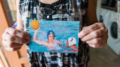 Lynn Whittaker holds an old photograph of her son playing water polo.