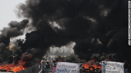 "Villagers mount roadblocks with burning tires to protest an army crackdown the day after a clash between soldiers and alleged fuel thieves known as ""huachicoleros"", who tap the pipelines of state-owned oil giant PEMEX, in Palmarito Tochapan, Puebla, Mexico on May 4, 2017.  Two soldiers were killed and another wounded Wednesday by a group of fuel thieves in a town in the Mexican state of Puebla in central Mexico, military officials said. / AFP PHOTO / JOSE CASTAÑARES        (Photo credit should read JOSE CASTANARES/AFP/Getty Images)"