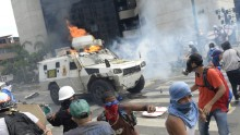 A charging National Guard riot control vehicle is hit by a Molotov cocktail thrown by a demonstrator during a protest against Venezuelan President Nicolas Maduro, in Caracas on May 3, 2017. Venezuela's angry opposition rallied Wednesday vowing huge street protests against President Nicolas Maduro's plan to rewrite the constitution and accusing him of dodging elections to cling to power despite deadly unrest. / AFP PHOTO / FEDERICO PARRA        (Photo credit should read FEDERICO PARRA/AFP/Getty Images)