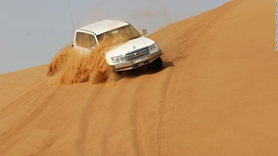 Four Wheel Drives race through the desert as they partake in 'Dunebashing'. Dune bashing is one of the most popular pastimes for tourists when they visit the desert, and involves vehicles driving at high speed over the undulating landscape.