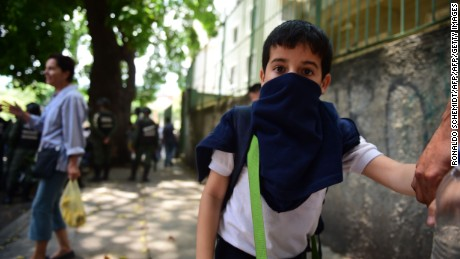 A child covers his nose and mouth to avoid breathing tear gas shot by police at opponents of Venezuelan President Nicolas Maduro marching in Caracas on April 26, 2017. Protesters in Venezuela plan a high-risk march against President Maduro Wednesday, sparking fears of fresh violence after demonstrations that have left 26 dead in the crisis-wracked country. / AFP PHOTO / RONALDO SCHEMIDT        (Photo credit should read RONALDO SCHEMIDT/AFP/Getty Images)