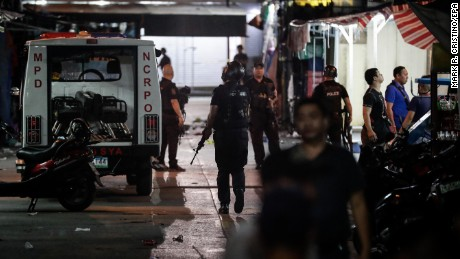 Members of a police bomb squad and SWAT team secure an area after an explosion Saturday in Manila.