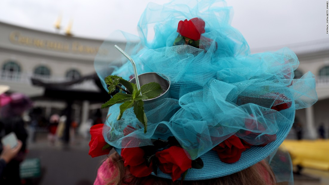 "A woman uses her festive hat as a cup holder before the race. The <a href=""https://www.kentuckyderby.com/history/traditions/mint-julep"" target=""_blank"">mint julep</a> is the traditional beverage of Churchill Downs and the Kentucky Derby."