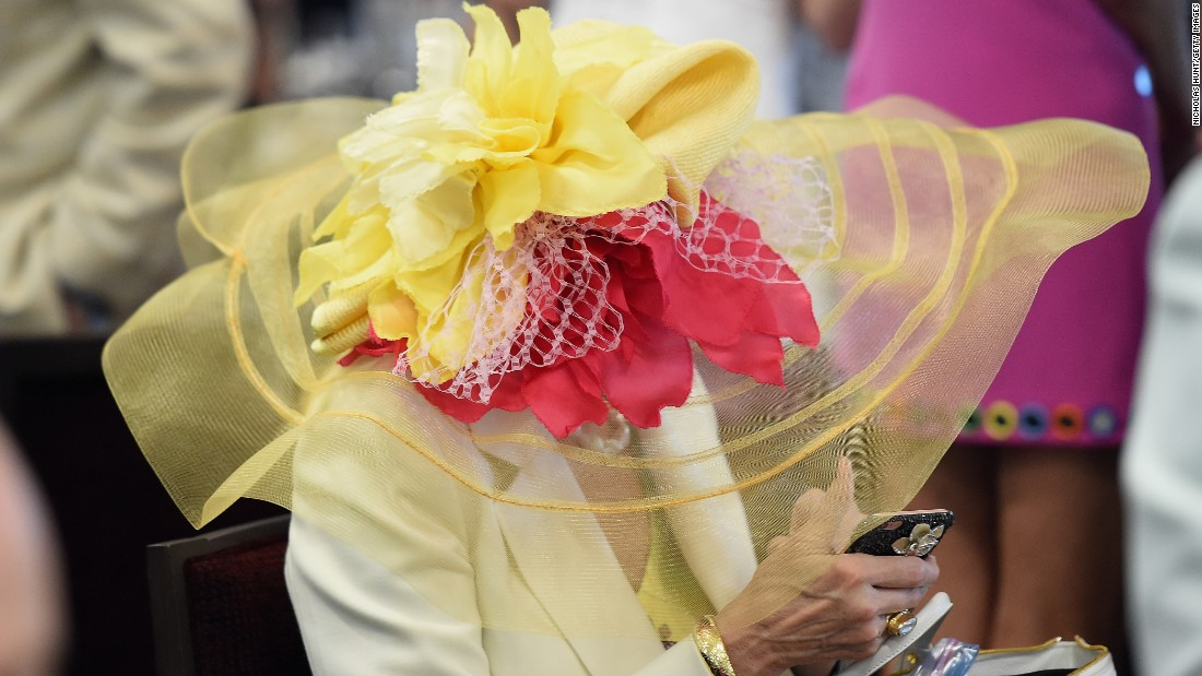 A derby attendee is concealed by the brim of her hat.