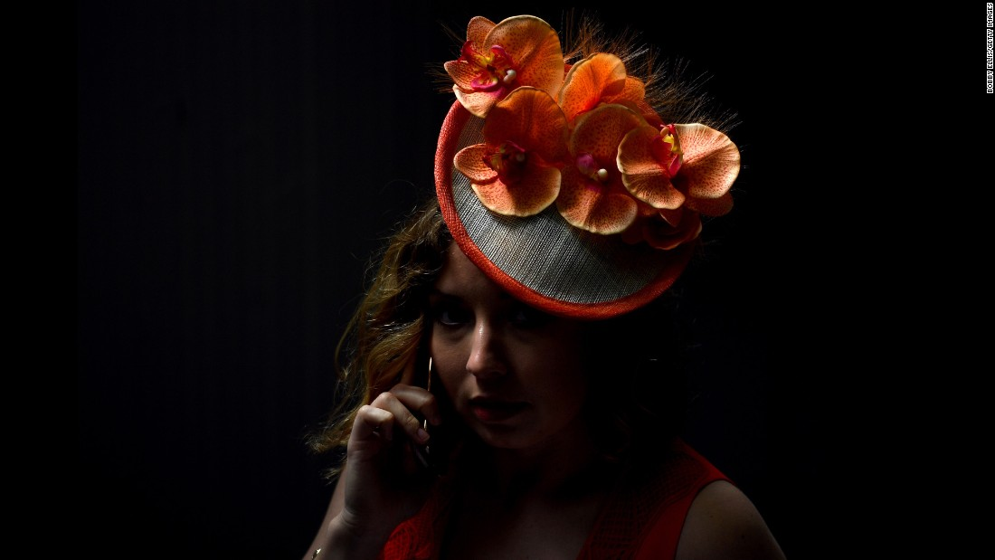 A woman displays orange orchids on her hat.