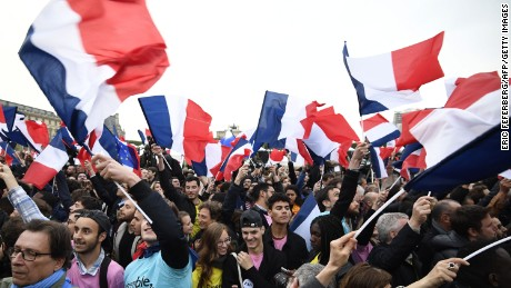 Supporters of French presidential election candidate for the En Marche ! movement Emmanuel Macron wave French national flags as they celebrate in front of the Pyramid at the Louvre Museum.