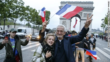 A man, flanked by a young woman, waves a French national flag next to people gesturing and shouting on the French avenue of the Champs Elysees by the Arc de Triomphe.