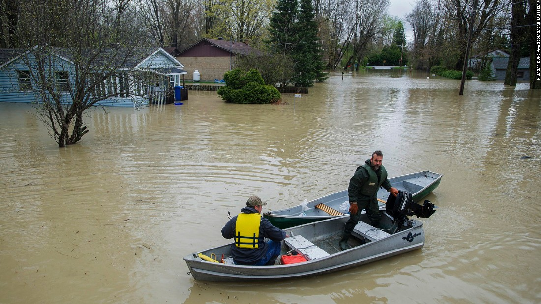 Two men navigate a flooded street in Rigaud on May 7.